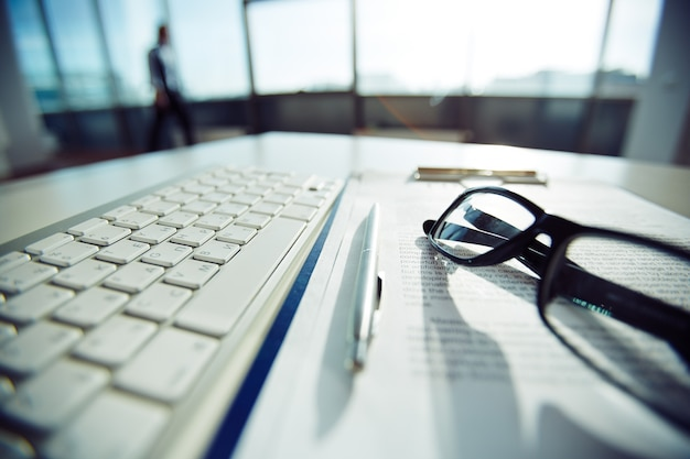 Primer plano de teclado y gafas en la mesa