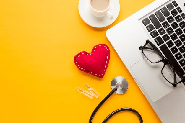 Primer plano del teclado del portátil; juguete de tela cosido; taza de café; ampolla; estetoscopio contra escritorio amarillo