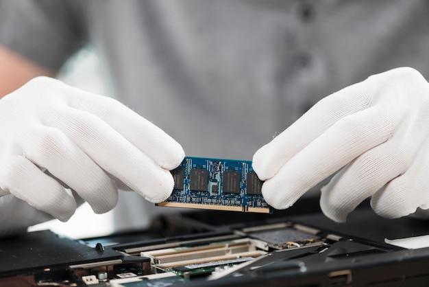 Primer plano de un técnico con chip de computadora