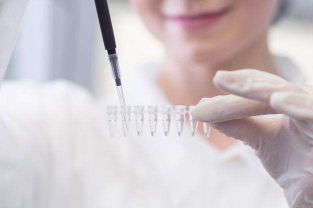 Primer plano de técnico femenino con multipipeta y en laboratorio genético haciendo investigación de pcr