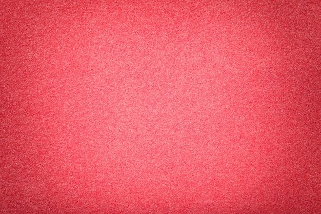Primer plano de tela de gamuza mate rojo claro. textura de terciopelo de fieltro.