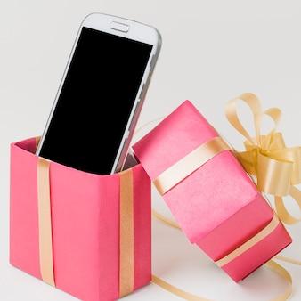 Primer plano de un teléfono celular en caja de regalo rosa decorada contra superficie blanca