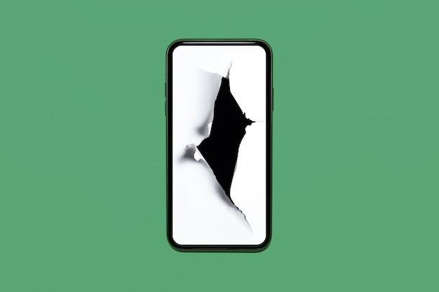 Primer plano del teléfono inteligente con agujero en papel blanco en pantalla, aislado sobre fondo verde pastel.