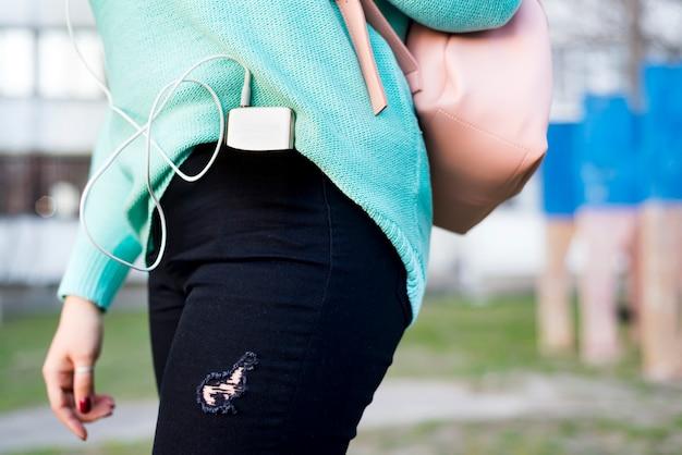 Primer plano de un teléfono inteligente en el bolsillo trasero de los jeans de una mujer,
