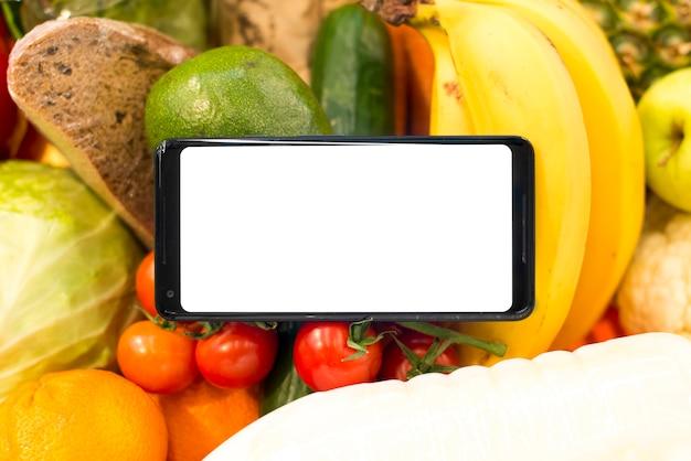 Primer plano de teléfono inteligente en frutas y verduras