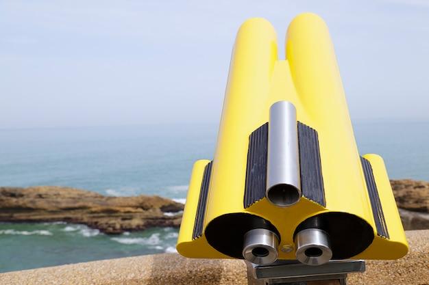 En primer plano, un telescopio que funciona con monedas en el fondo una vista de la roca de la virgen maría en biarritz, francia