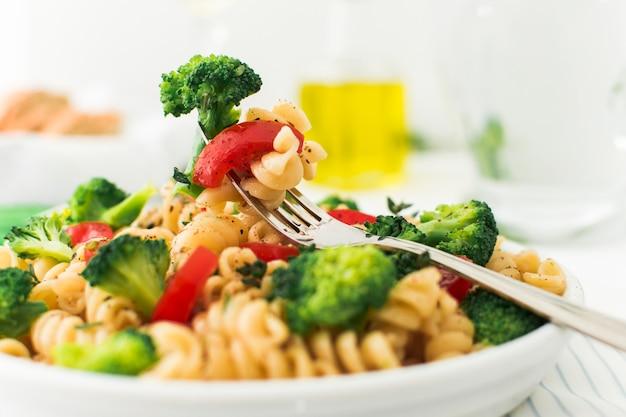 Primer plano de tenedor con brócoli; tomate y fusilli en plato blanco.