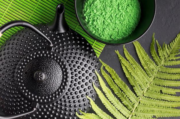 Primer plano de tetera con polvo de té verde partido y hojas de helecho