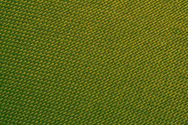 Primer plano textil amarillo y verde. fondo de fibra tejida, superficie de tela trenzada, papel tapiz de arpillera natural. textura de material de lino macro.
