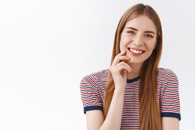 Primer plano tierna, femenina joven feliz con camiseta a rayas, cabello largo castaño, dientes sonrientes, inclinar la cabeza entretenido, tocar la mejilla levemente con una mirada linda, tener una conversación agradable