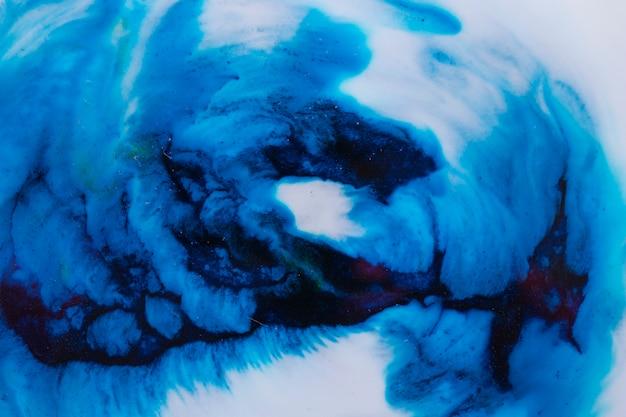 Primer plano de tinta azul se disuelve en pintura líquida blanca.