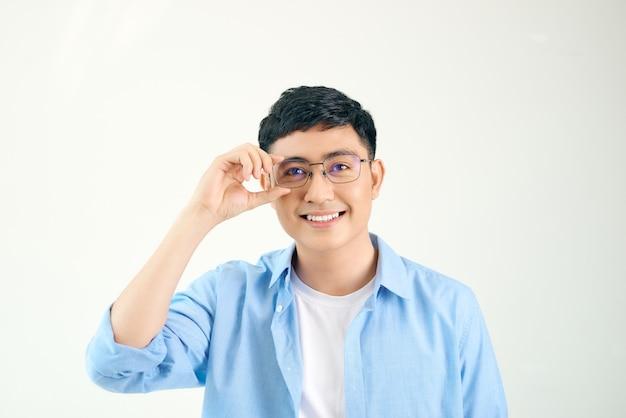 Primer plano de un tipo amable con anteojos. joven asiático ajustando gafas y mirando a través de la lente. concepto de visión y cuidado de los ojos