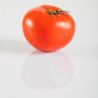 Primer plano de un tomate rojo fresco sobre fondo blanco