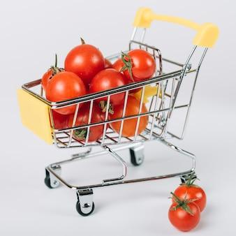 Primer plano de tomates frescos en carretilla en superficie blanca