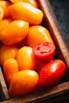 Primer plano de tomates pequeños naranjas y rojos