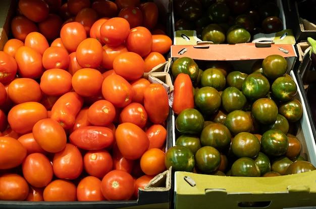 Primer plano de tomates rojos suaves y variedad verde de tomates en el mostrador de la tienda de comestibles