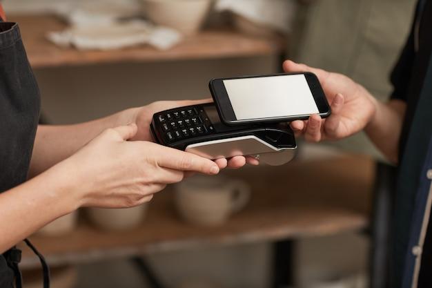 Primer plano de tonos cálidos del cliente pagando a través de un teléfono inteligente con pantalla en blanco en el taller de cerámica, espacio de copia