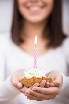 Primer plano de la torta de cumpleaños. la mujer joven está sosteniendo la torta.