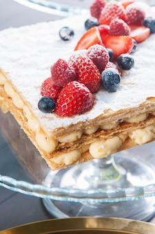 Primer plano de la torta de napoleón con crema de crema y bayas maduras