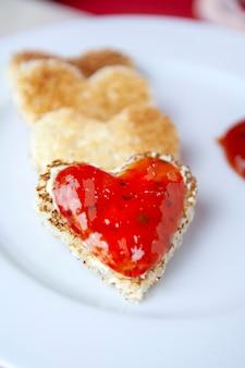 Primer plano de tostadas en forma de corazón y mermelada de fresa