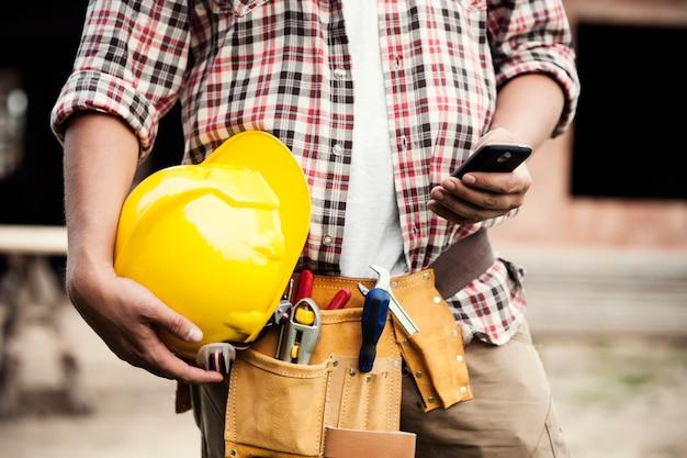 Primer plano, de, trabajador de la construcción, mensajes de texto, en, teléfono móvil