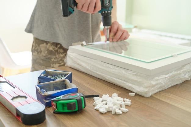 Primer plano de un trabajador manual haciendo muebles, montaje de cocina con herramientas profesionales