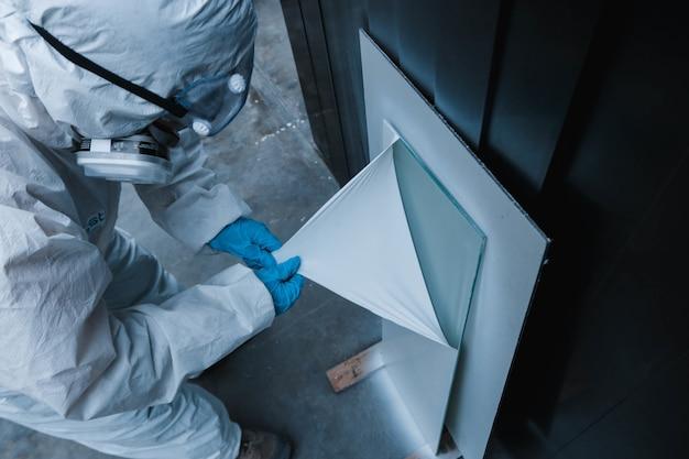 Primer plano de un trabajador con un traje de materiales peligrosos arrancando una capa protectora