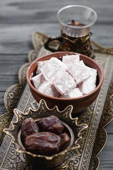 Primer plano de la tradicional delicia turca lukum; fechas y té en bandeja metálica.