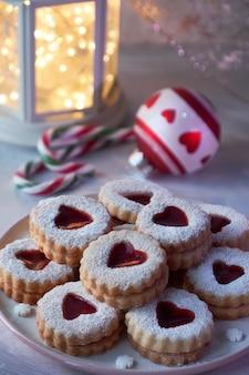 Primer plano de las tradicionales galletas de navidad linzer rellenas de mermelada roja en la mesa de luz con decoraciones de navidad