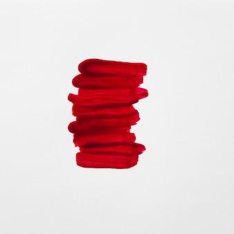 Primer plano de trazos de barniz de uñas rojo sobre fondo blanco