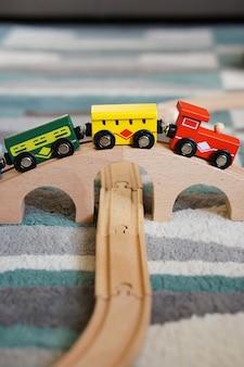 Primer plano de un tren de juguete sobre un puente de madera