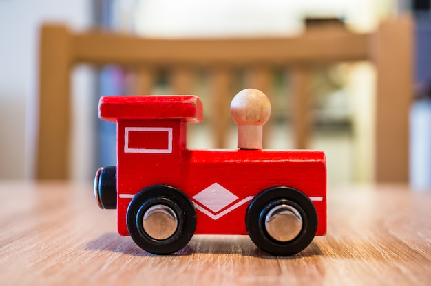 Primer plano de un tren de madera de juguete rojo sobre una mesa de madera