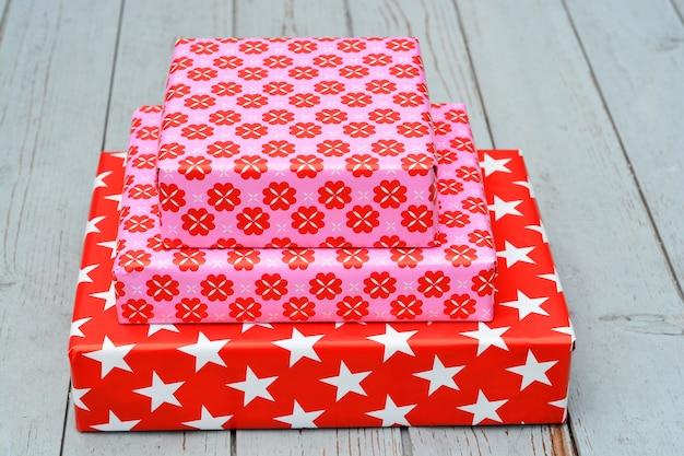 Primer plano de tres cajas de regalo apiladas una encima de la otra sobre una superficie de madera