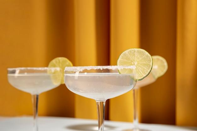 Primer plano de tres copas de cóctel margarita con borde salado y limón