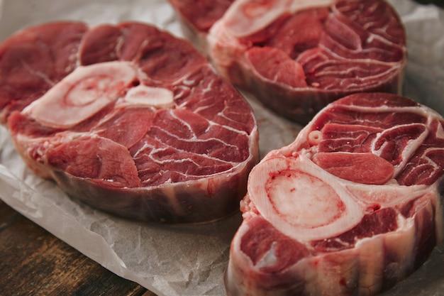 Primer plano tres filetes de carne cruda fresca con hueso sobre papel blanco desde la parte superior