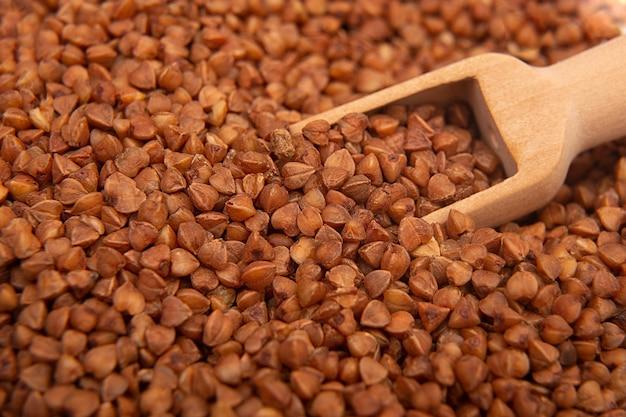 Primer plano de trigo sarraceno seco con una cuchara de madera