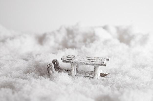 Primer plano de un trineo en la nieve, juguetes decorativos de navidad en el fondo blanco.