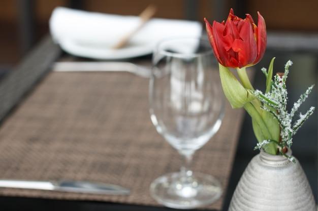 Primer plano de un tulipán rojo en un pequeño jarrón sobre la mesa con una copa de vino en una cafetería o restaurante