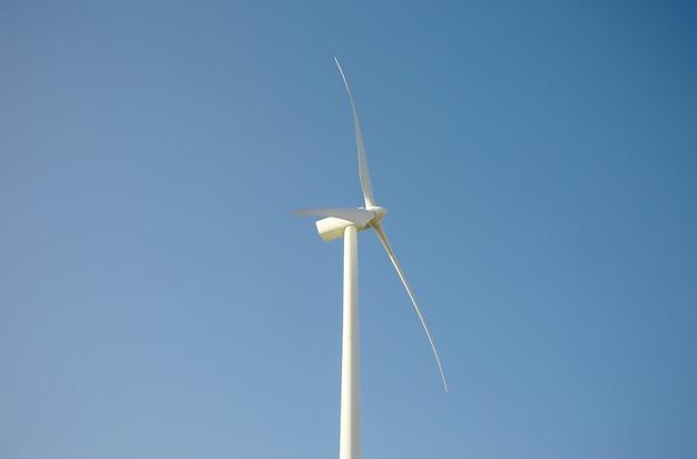 Primer plano de una turbina de molino de viento y palas que generan electricidad sobre un fondo de cielo azul. concepto de producción de energía limpia y ecológica.
