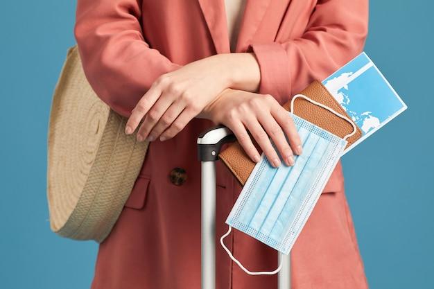Primer plano de turista con pasaporte y billetes de avión de pie contra el fondo azul.