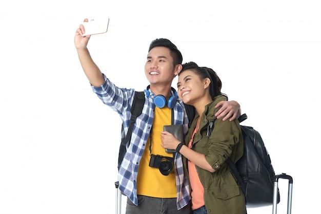 Primer plano de turistas asiáticos tomando un selfie sobre fondo blanco.