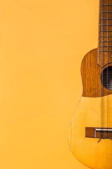 Primer plano de ukelele de madera sobre fondo amarillo