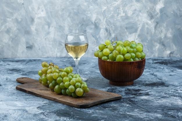 Primer plano de uvas blancas en un tazón con copa de vino, uvas en una tabla de cortar sobre fondo de mármol azul claro y oscuro. horizontal