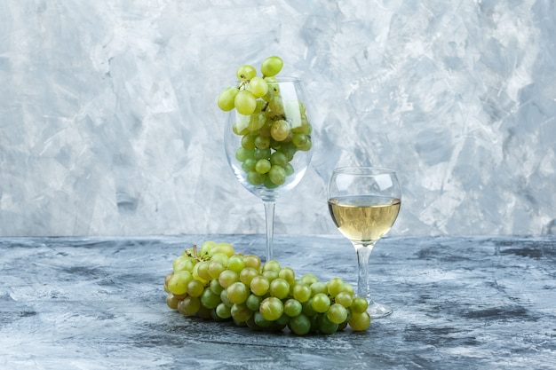 Primer plano de uvas blancas, vaso de whisky sobre fondo de mármol azul claro y oscuro. horizontal