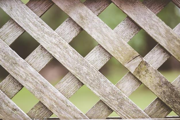 Primer plano de una valla entrecruzada de madera con un borroso