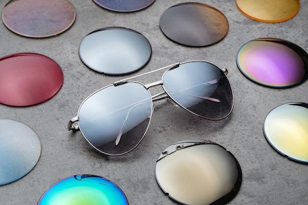 Primer plano de una variedad de lentes correctivos ópticos de diferentes colores para gafas, gafas de sol de moda para la protección de los ojos del sol