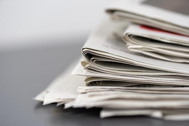 Primer plano de varios periódicos apilados uno encima del otro