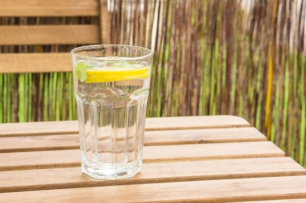 Primer plano de un vaso de agua con limón y menta en un banco de madera