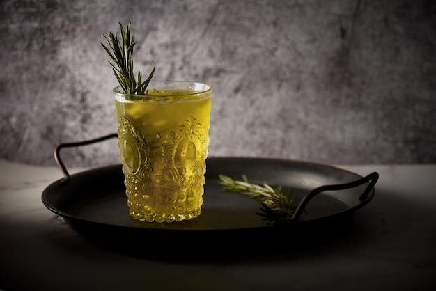 Primer plano de un vaso de bebida amarilla con hojas de romero