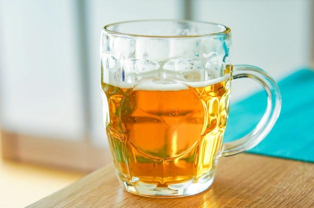 Primer plano de un vaso de cerveza en una mesa de madera